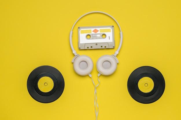 Casque avec une cassette et deux disques vinyle sur fond jaune. appareils rétro pour stocker et lire des enregistrements audio.