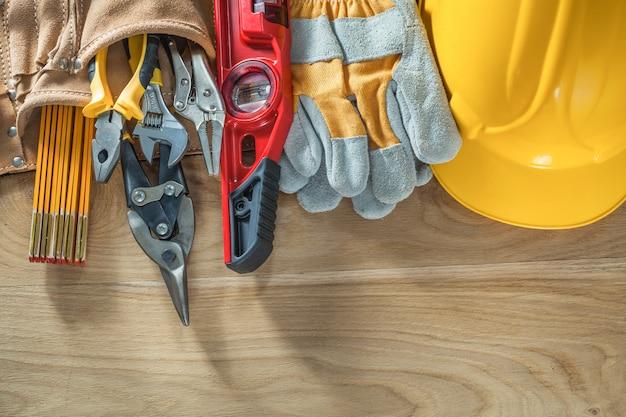 Casque de construction gants de sécurité ceinture à outils niveau construction sur planche de bois