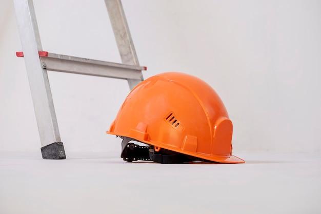 Le casque de construction se trouve contre le mur de plâtre