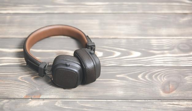 Casque en cuir marron sur fond en bois vintage. concept de musique moderne.