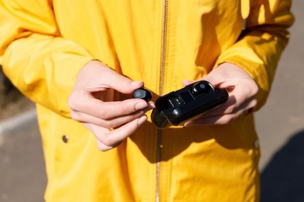 Casque dans les mains d'une femme en imperméable jaune. fermer