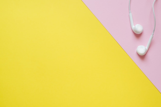 Casque du joueur sur une table rose et jaune avec une copie de l'espace. concept d'éducation, école et bureau