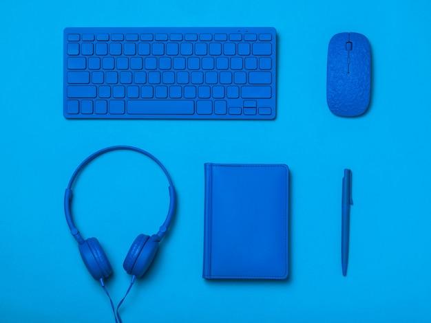 Casque d'écoute de souris clavier et bloc-notes avec un stylo de couleur bleue sur une surface bleue. image monochrome d'accessoires de bureau.