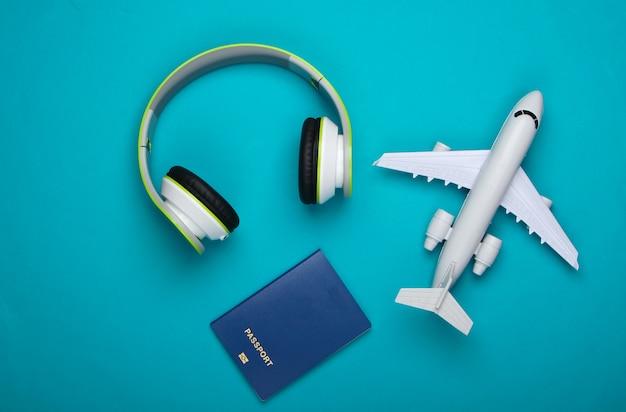 Casque, figurine d'avion, passeport sur surface bleue