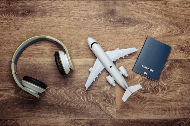 Casque, figurine d'avion, passeport sur une surface en bois