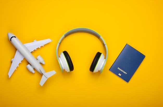 Casque, figurine d'avion, passeport sur surface jaune