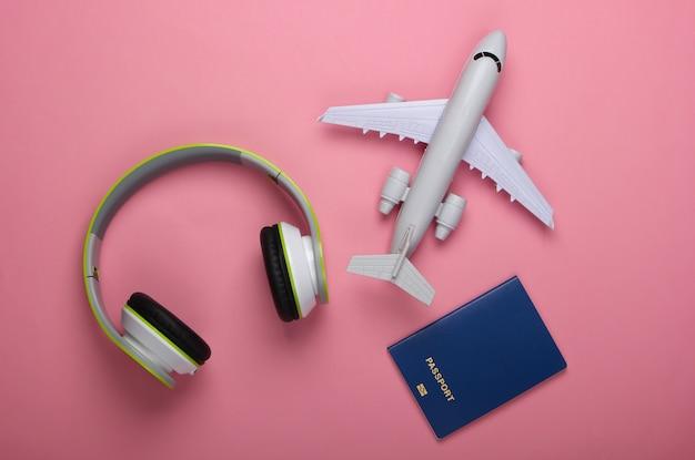 Casque, figurine d'avion, passeport sur une surface rose pastel