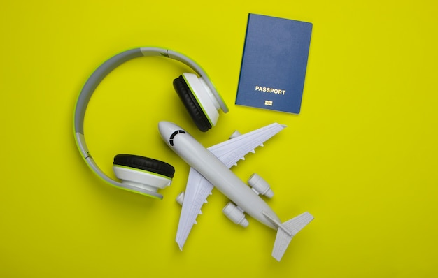 Casque, figurine d'avion, passeport sur surface verte
