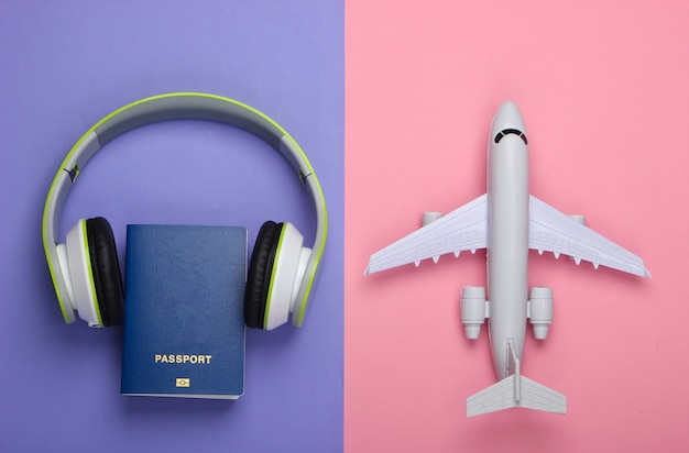 Casque, figurine d'avion, passeport sur surface violette et rose