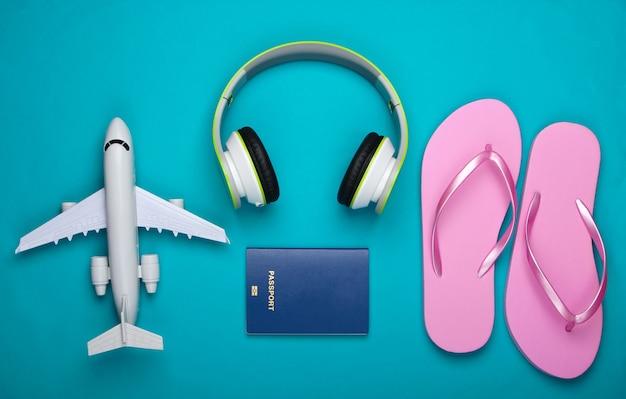 Casque, figurine d'avion, passeport, tongs sur surface bleue