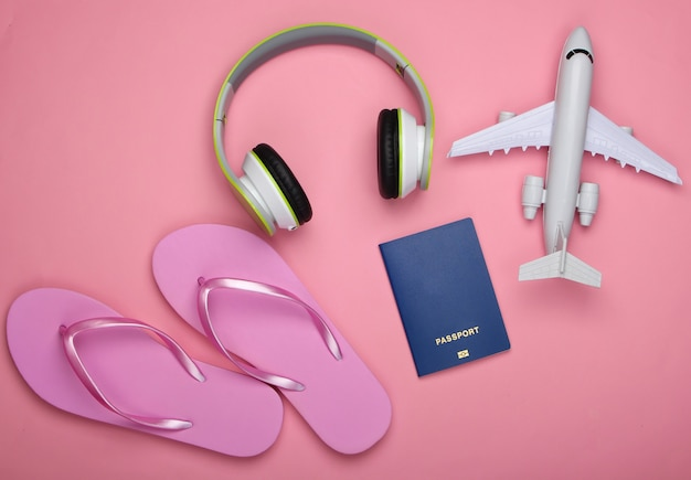Casque, figurine d'avion, passeport, tongs sur une surface rose pastel