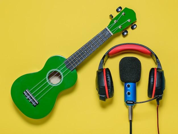 Casque filaire bleu micro filaire et ukulélé guitare vert sur fond jaune. équipement pour enregistrer des morceaux de musique. la vue du haut. mise à plat.
