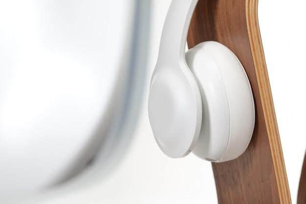 Casque hifi (high fidelity) sur un support en bois oméga. casque d'écoute hifi isolé haute fidélité (haute fidélité) sur un support en bois oméga. isolé