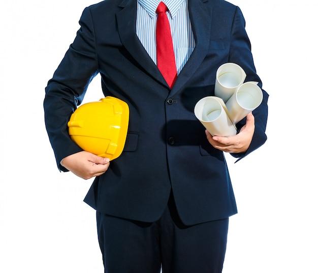 Casque ingénieur jaune pour la sécurité des travailleurs avec des plans de construction isolés
