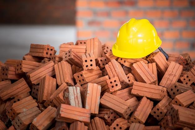 Casque jaune placé sur un tas de briques ou de briques en argile orange. le matériau de base de la construction est le chantier.