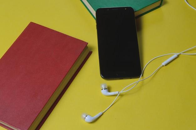 Casque avec des livres et un smartphone sur fond jaune.