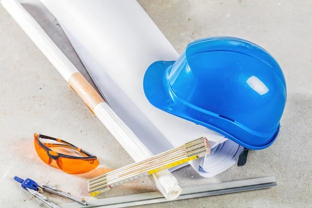 Un casque, des lunettes et des plans sur le chantier de construction.