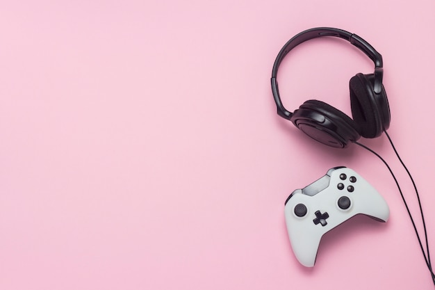 Casque et manette de jeu sur fond rose. le concept du jeu sur console, divertissement, loisirs, jeux en ligne. mise à plat, vue de dessus.