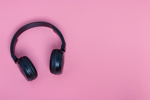 Casque noir sur fond rose avec espace de copie. notion musicale.