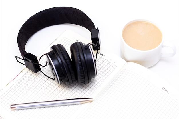 Casque noir avec une tasse de café sur une surface blanche. cahier avec stylo sur la table
