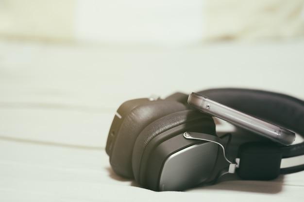 Casque noir avec téléphone intelligent tout en jouant de la musique, un clip vidéo ou un podcast et un film. lumière vintage