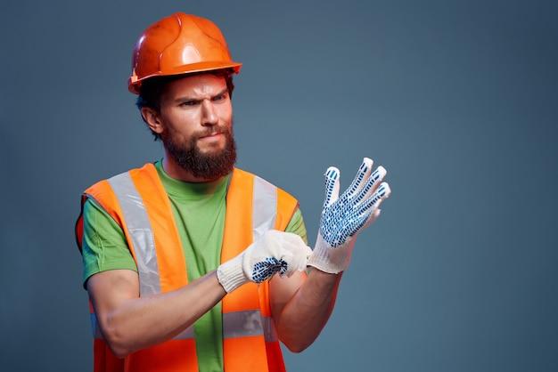 Casque orange de constructeur masculin sur le fond isolé de l'industrie de la tête