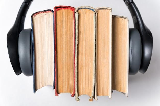 Casque porté sur une pile de vieux livres sur un gros plan de surface blanche. concept de livres audio. vue de dessus