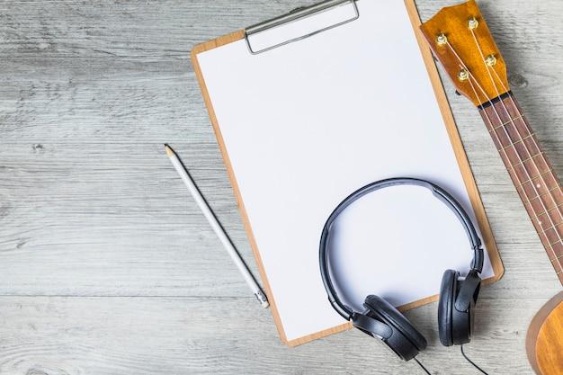 Casque sur presse-papiers avec poupée guitare et crayon sur fond en bois