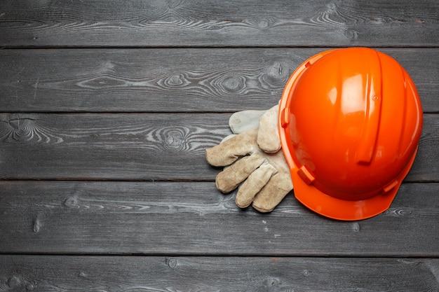 Casque de protection et paire de gants de travail sur une surface en bois