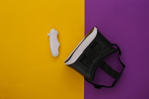 Casque de réalité virtuelle avec contrôleur sur fond jaune-violet. vue de dessus. flay jeter