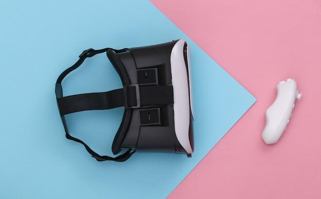Casque de réalité virtuelle avec joystick sur fond pastel bleu rose. vue de dessus. flay jeter. minimalisme