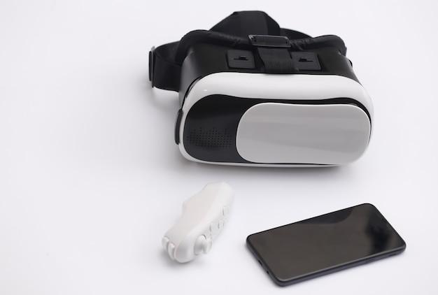 Casque de réalité virtuelle avec joystick et smartphone sur fond blanc. gadgets modernes