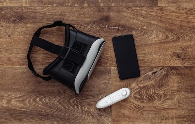 Casque de réalité virtuelle avec joystick et smartphone sur fond en bois. gadgets modernes