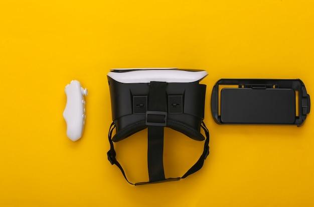 Casque de réalité virtuelle avec joystick et smartphone sur fond jaune. gadgets modernes. vue de dessus