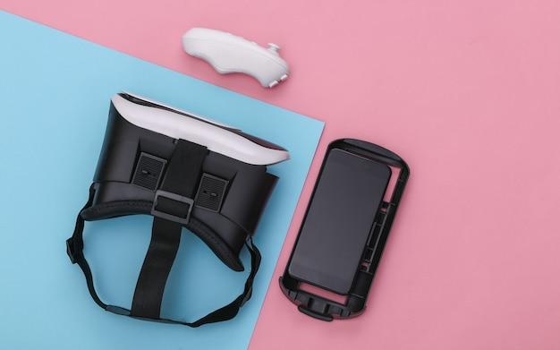 Casque de réalité virtuelle avec joystick et smartphone sur fond pastel bleu rose. gadgets modernes. vue de dessus