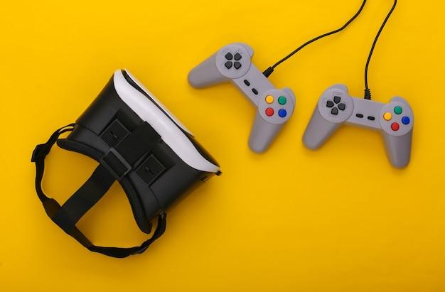 Casque de réalité virtuelle, manettes de jeu rétro sur fond jaune. divertissement, jeu vidéo 3d. vue de dessus