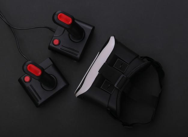 Casque de réalité virtuelle et manettes rétro sur fond noir. divertissement, jeu vidéo. vue de dessus