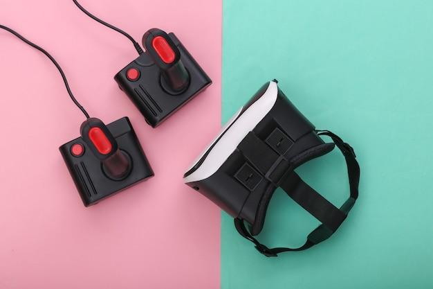 Casque de réalité virtuelle et manettes rétro sur fond pastel bleu rose. divertissement, jeu vidéo. vue de dessus