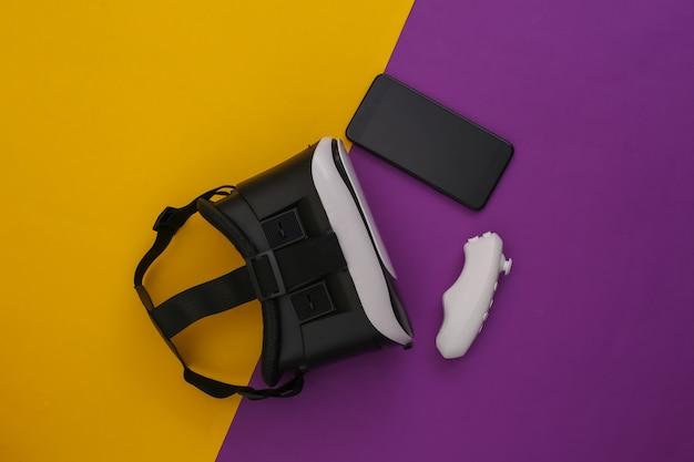 Casque de réalité virtuelle avec smartphone, contrôleur sur fond jaune-violet. vue de dessus. flay jeter