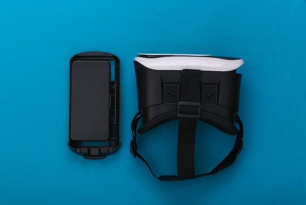 Casque de réalité virtuelle et smartphone sur fond bleu. gadgets modernes. vue de dessus