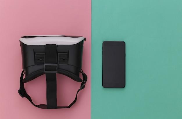 Casque de réalité virtuelle avec smartphone sur fond bleu rose. vue de dessus. flay jeter