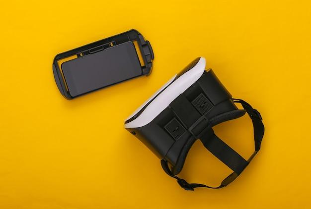 Casque de réalité virtuelle et smartphone sur fond jaune. gadgets modernes. vue de dessus