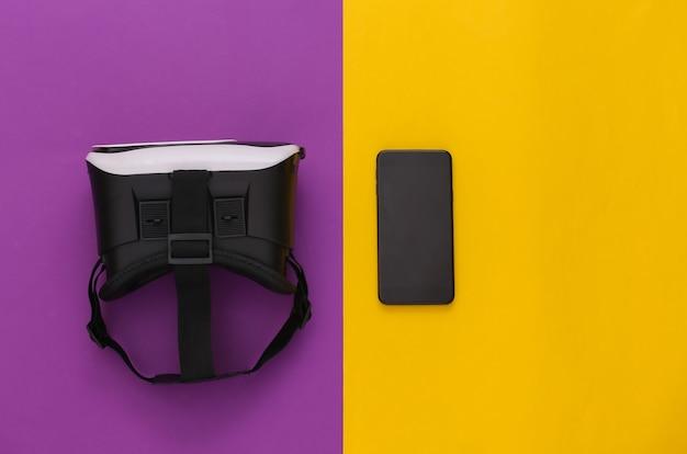 Casque de réalité virtuelle avec smartphone sur fond jaune-violet. vue de dessus. flay jeter