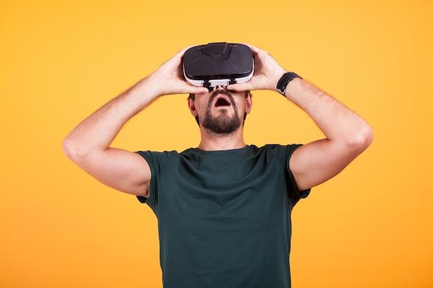 Casque de réalité virtuelle vr sur la tête d'un homme étonné qui l'essaye pour la première fois. gadget de lunettes innovant