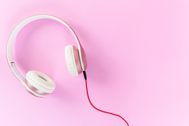 Casque rose et câble rouge sur fond de couleur rose pastel. concept de musique.