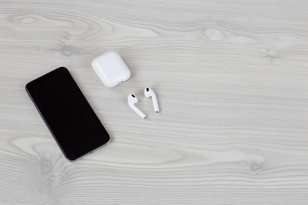 Sur un casque sans fil à fond clair, un téléphone portable et un espace libre pour le texte