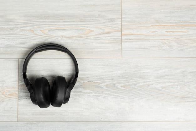 Casque sans fil sur fond de sol stratifié en bois blanc insonorisation musique et son dans le...