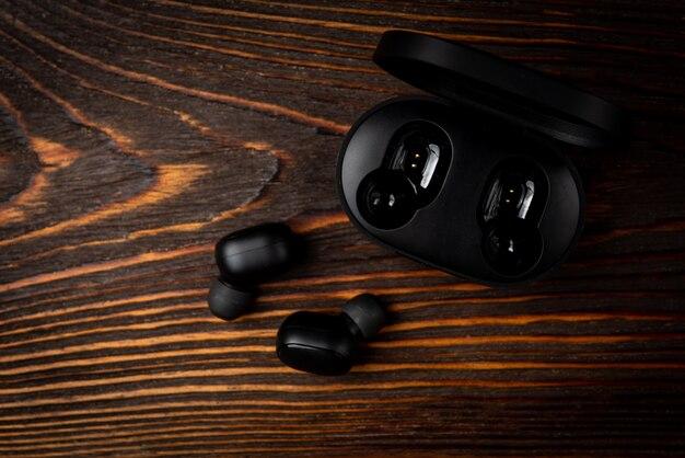 Casque sans fil noir sur fond en bois foncé.