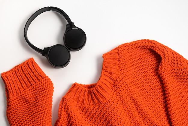 Casque sans fil en pull noir et orange sur fond blanc technologie moderne vue de dessus plat lay