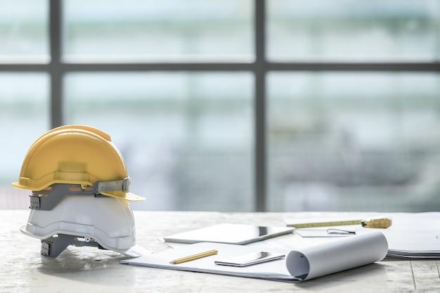 Casque de sécurité blanc et jaune sur le chantier, lumière d'une grande fenêtre en arrière-plan